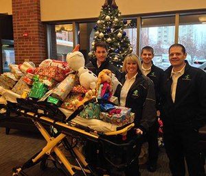 Ada County Paramedics stand with a toy-filled gurney for children hospitalized over the holidays.