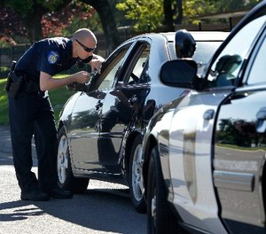 In this Nov. 12, 2012 file photo, a police officer makes a traffic stop in Sacramento, Calif. (AP Photo/Rich Pedroncelli, File)