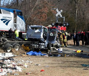 Emergency personnel work at the scene of a train crash involving a garbage truck in Crozet, Va.