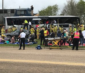 Emergency personnel assist injured passengers after their charter bus collided with a train in Biloxi, Miss., Tuesday, March 7, 2017. (John Fitzhugh/Sun Herald via AP)