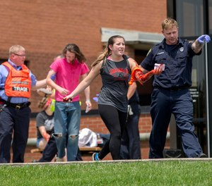 In a May 25, 2016 file photo, an emergency worker directs a volunteer with simulated injuries during a training exercise for an active shooter at Hopewell Elementary School, in West Chester, Ohio.