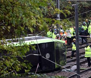 Emergency service workers attend the scene of a derailed tram in Croydon, south London.