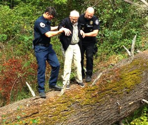 A firefighter and police officer help the man off of the fallen tree he had climbed. (Image courtesy Gresham Police Department)