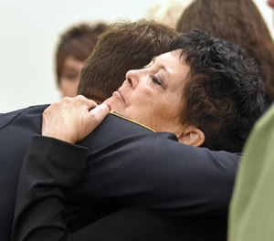 """In this Sept. 8, 2016 file photo Julie Benner, widow of police officer Gregg """"Nigel"""" Benner, is given support by members of the Rio Rancho Police Department in a Los Lunas, N.M., courtroom on the first day of testimony in the trial of Andrew Romero for the shooting death of Benner. (AP File Photo/The Albuquerque Journal)"""