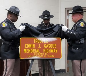 A Florida Highway Patrol honor guard unveils a sign memorializing Trooper Edwin J. Gasque, shot and killed on Oct. 26, 1961, when he was ambushed. (Photo/TNS)