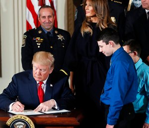 President Donald Trump signs a presidential memorandum declaring the opioid crisis a public health emergency in the East Room of the White House.