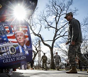 Military personnel walk along the National Mall in Washington, Wednesday, Jan. 18, 2017, alongside vendors selling President-elect Donald Trump merchandise ahead of Friday's presidential inauguration. (AP Photo/John Minchillo)