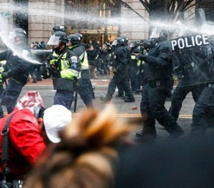 In this Jan. 20, 2017, file photo, police fire pepper spray at protestors during a demonstration in downtown after the inauguration of President Donald Trump.