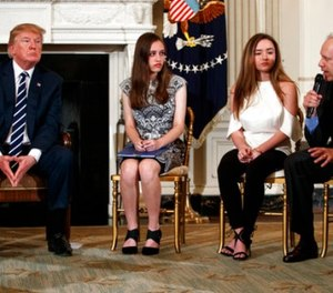 From left, President Donald Trump, Marjory Stoneman Douglas High School student students Carson Abt, and Ariana Klein, listen as Carson's father Frederick Abt, speaks during a listening session with high school students, teachers, and others in the State Dining Room of the White House in Washington, Wednesday, Feb. 21, 2018. (AP Photo/Carolyn Kaster)