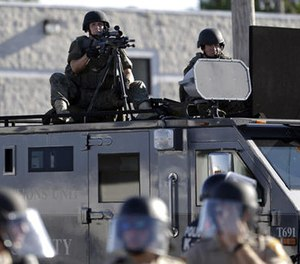 In this Aug. 9, 2014 file photo, a police tactical team moves in to disperse a group of protesters in Ferguson, Mo. that was sparked after Michael Brown, an unarmed black man was shot and killed by Darren Wilson, a white Ferguson police officer.