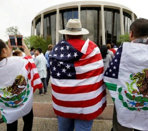 In this June 26, 2017, file photo, protesters outside the federal courthouse in San Antonio, Texas, take part in a rally to oppose a new Texas