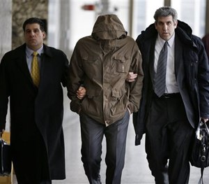 In this Feb. 27, 2014, file photo, Wojciech Braszczok, center, is led into the courtroom while covering his face in New York. (AP Image)