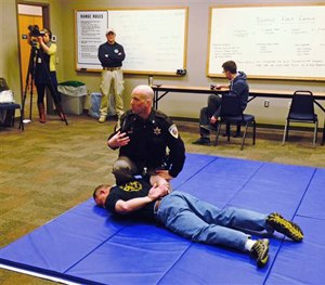 Dane County Sheriff's Deputy Eric Markgraf demonstrates the steps police are taught to take after shooting someone, during a media training session in Waunakee, Wis.