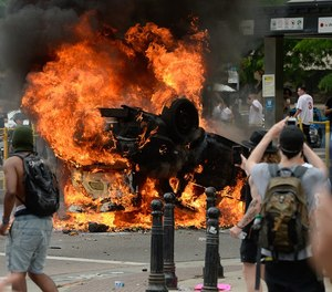 A police car burns during a protest that turned violent on May 30. Prosecutors charged an eighth person on Monday for the burning.