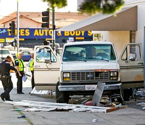 An official looks at a van that plowed into a group of people on a Los Angeles sidewalk. (AP Photo/Damian Dovarganes)