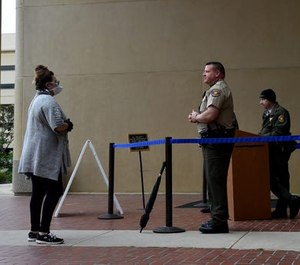 Jennifer Morrison, of Simi Valley, speaks with a Ventura County Sheriff's deputy at the entrance of Ventura County Superior Court on Friday. County law enforcement has asked the state to change bail rules due to high crime rates.
