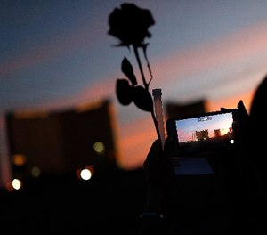 A woman takes a picture of the Mandalay Bay hotel and casino during a vigil for victims and survivors of the mass shooting in Las Vegas, Sunday, April 1, 2018, in Las Vegas.