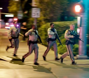 In this Oct. 1, 2017, file photo, police run toward the scene of a mass shooting near the Mandalay Bay resort and casino on the Las Vegas Strip in Las Vegas.