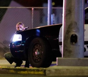 A police officer takes cover behind a police vehicle during a shooting near the Mandalay Bay resort and casino on the Las Vegas Strip, Sunday, Oct. 1, 2017, in Las Vegas. (AP Photo/John Locher)