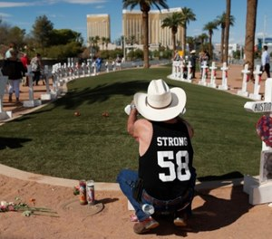 Jim Strickland, of Oroville, Calif., writes a message on a cross at a makeshift memorial for victims of the Oct. 1, 2017, mass shooting in Las Vegas, Sunday, Sept. 30, 2018, in Las Vegas. (AP Photo/John Locher)