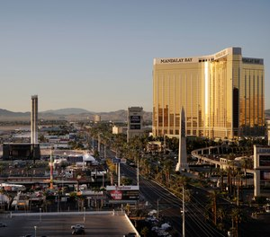 This Oct. 3, 2017, file photo shows the Mandalay Bay resort and casino, right, overlooking an outdoor festival grounds across the street, left, in Las Vegas.