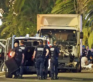 Police stand by as medical personnel attend a person on the ground, right, in the early hours of Friday, July 14, 2016, on the Promenade des Anglais in Nice, southern France, next to the lorry that had been driven into crowds of revelers late Thursday.