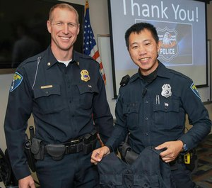 Deputy Chief of Police Matt Rokus (left) issues Eau Claire police officer Mark Vang his load-bearing vest.