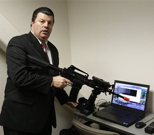 Bob Walker, of Cole Engineering Services, Inc., displays an AR-15 that will be used by police in a virtual first-person computer training program.