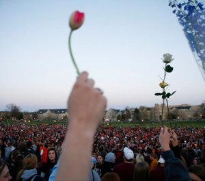 In this Tuesday, April 17, 2007 file photo, People gather for a vigil on the drill field following the shootings on the Virginia Tech campus in Blacksburg, Va. (AP Photo/Casey Templeton, File)