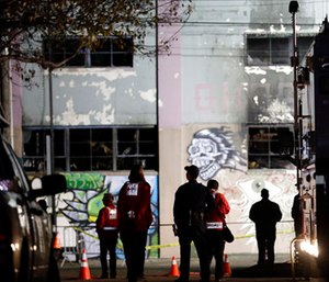 Emergency crews stand in front of the site of a warehouse fire in Oakland, Calif.