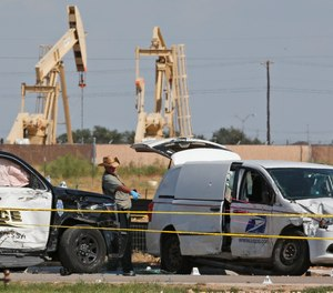 In this Sunday, Sept. 1, 2019, file photo, law enforcement officials process the crime scene from Saturday's shooting which ended with the shooter, Seth Ator, being shot dead by police in a stolen mail van, right, in Odessa, Texas.