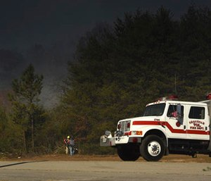 Volunteer firefighters Sheri Torbett and Jeannie Vaughn, left, with the Sequoyah Volunteer Fire Department, use leaf blowers remove debris off the break near the Mowbray Volunteer Fire Hall in Soddy-Daisy, Tenn. (Tim Barber /Chattanooga Times Free Press via AP)