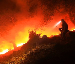 A San Diego Cal Fire firefighter monitors a flare up on a the head of a wildfire.