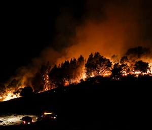 Firefighters watch from their fire trucks as wildfires continue to burn near Calistoga, Calif.