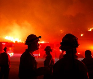Firefighters gather in front of a residential area as a wildfire burns along the 101 Freeway. (AP Photo/Jae C. Hong)