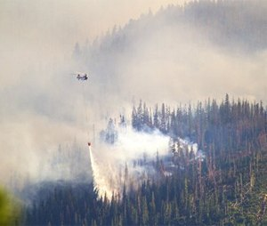 A helicopter dumps a load of water onto one of the fires burning on a ridge west of Leavenworth, Wash. (AP Photo/The Seattle Times, Mike Siegel)