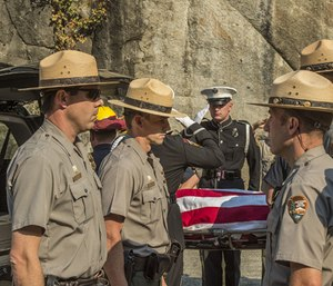 In this Oct. 8, 2014, file photo, Yosemite National Park Rangers transfer the body of a Cal Fire pilot who was killed in an airplane crash in Yosemite National Park, Calif. An investigation into the 2014 fatal crash found that the pilot was warned to avoid a hazardous tree to the right of his flight path before a wing struck trees to the left. (AP Photo/Al Golub, File)