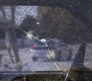 A car is seen through the window of a pickup truck shattered by bullets fired during a police shootout with San Bernardino shooting rampage suspects Syed Farook and his wife, Tashfeen Malik, Saturday, Dec. 5, 2015, in San Bernardino, Calif.