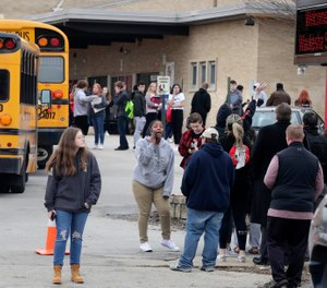 Waukesha South High School students find their waiting parents and friends and hug after they leave the building following shots fired inside the school. (Photo/AP)
