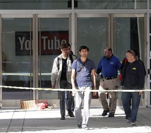 A group walks out of a YouTube office building in San Bruno, Calif., Wednesday, April 4, 2018.
