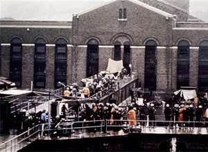 In this Sept. 13, 1971 file photo, correctional officers and New York State troopers gather outside Attica State Prison as they prepare to enter the prison and retake it after inmates rioted and held the prison for five days, in Attica, N.Y.
