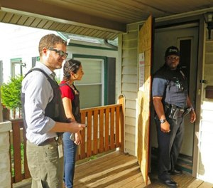 Milwaukee prosecutor Jeremy Arn, left, Safe & Sound coordinator Claudia Pizano, center, and police officer Chauncey Harris prepare to enter a vacant home on the city's north side after neighbors expressed concern about possible criminal activity.