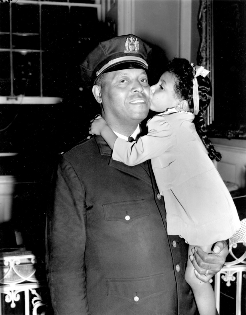 In this Sept. 4, 1941 file photo, Lt. Samuel Battle gets a kiss from his 4-year-old granddaughter, Yvonne, at City Hall in New York where he was sworn in as the first black parole commissioner in the city.