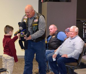 In this photo, a child of a fallen LEO recieves his custom bear. (Photo/Blue Line Bears)