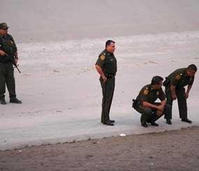 U.S. border patrol agents examine the area near where 14-year-old Mexican youth Sergio Adrian Hernandez Huereca was killed, allegedly shot by a U.S. Border Patrol agent after a confrontation under the Paso Del Norte border bridge in Ciudad Juarez. (AP Image)