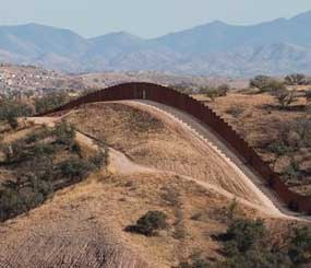 This file photo shows the border fence stretching west of Nogales, Ariz. into the Coronado National Forest. An Arizona lawmaker, Republican state Sen. Steve Smith, who is leading an effort to build additional fences near the state's border with Mexico through donations said he expects to begin construction on more barriers some time next year.