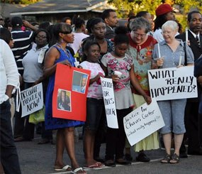 In this Aug. 6, 2012 file photo, supporters of Chavis Carter hold signs during a candlelight vigil at the First Baptist Church in Jonesboro, Ark. An autopsy report released Monday, Aug. 20, lists Carter's death as a suicide.