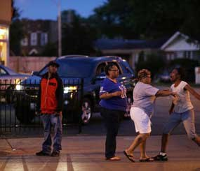Latayna Herring is held back after she broke down screaming at police near the scene where her 21-year-old son was shot and killed on Aug. 10 in Chicago.