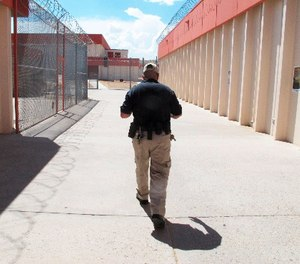 This Aug. 6, 2012 file photo shows a corrections officer walk through the Central New Mexico Corrections Facility in Los Lunas, N.M. (AP Photo/Russell Contreras)