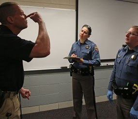 Simulating a roadside investigation of a potentially intoxicated driver, Colorado State Trooper Sgt. David Blatner, left, pretends to be high and struggling to touch his nose with his eyes closed as he trains troopers Carrie Jackson, center, and Toby Cox in a several week long Drug Recognition Expert class.